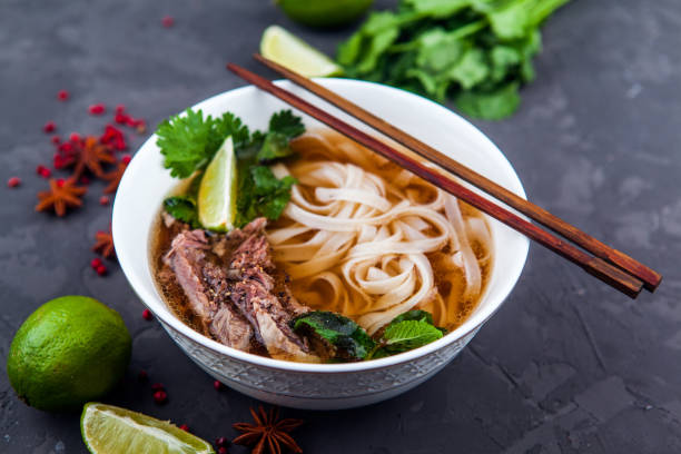 vietnamese beef noodle soup pho bo with beef on dark background - pho soup stock photos and pictures