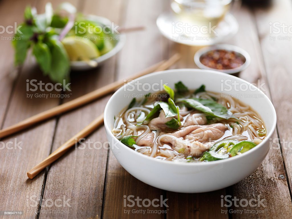vietnamese beef pho with chopsticks on wooden table stock photo