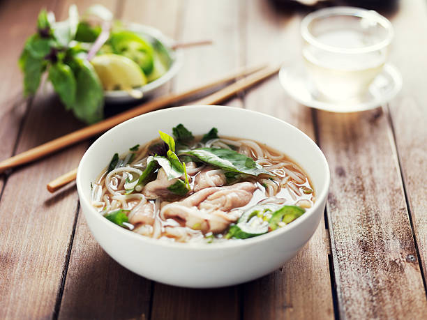 vietnamese beef pho with chopsticks on wooden table - pho soup stock photos and pictures
