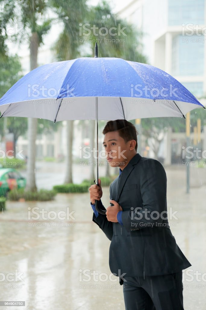 Vietnamese Businessman Standing in Pouring Rain royalty-free stock photo