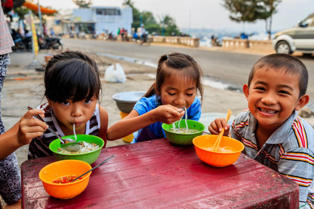 Vietnamese children eating a pho bo, South Vietnam Happy Vietnamese children eating a pho bo in local restaurant, next to the road, South Vietnam. Pho bo is a extremely popular Vietnamese noodle soup consisting of broth, rice noodles, herbs and beef meat. vietnamese culture stock pictures, royalty-free photos & images