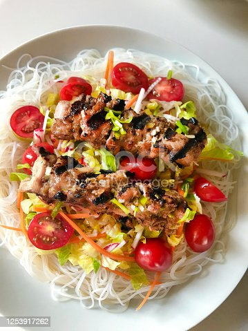 Bun Ga Nuong a popular Vietnamese dish of grilled chicken served on top of a bed of salad and chilled rice noodle and a savory spicy fish sauce dressing, a good healthy summer meal.