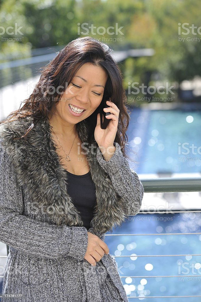 Vietnamese Chinese pretty woman talk on phone by pool royalty-free stock photo