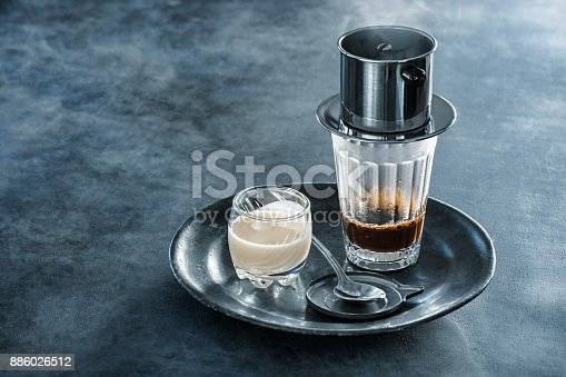 Hi resolution digital capture of coffee being prepared in the classic Vietnamese style.  The still steaming metal drip filter, known as phin cà phê sits on top of a glass, which sits on a small tray alongside a smaller glass containing sweetened condensed milk. This simple setup is the beginning for classic Vietnamese iced coffee, as well as several other coffee drinks.