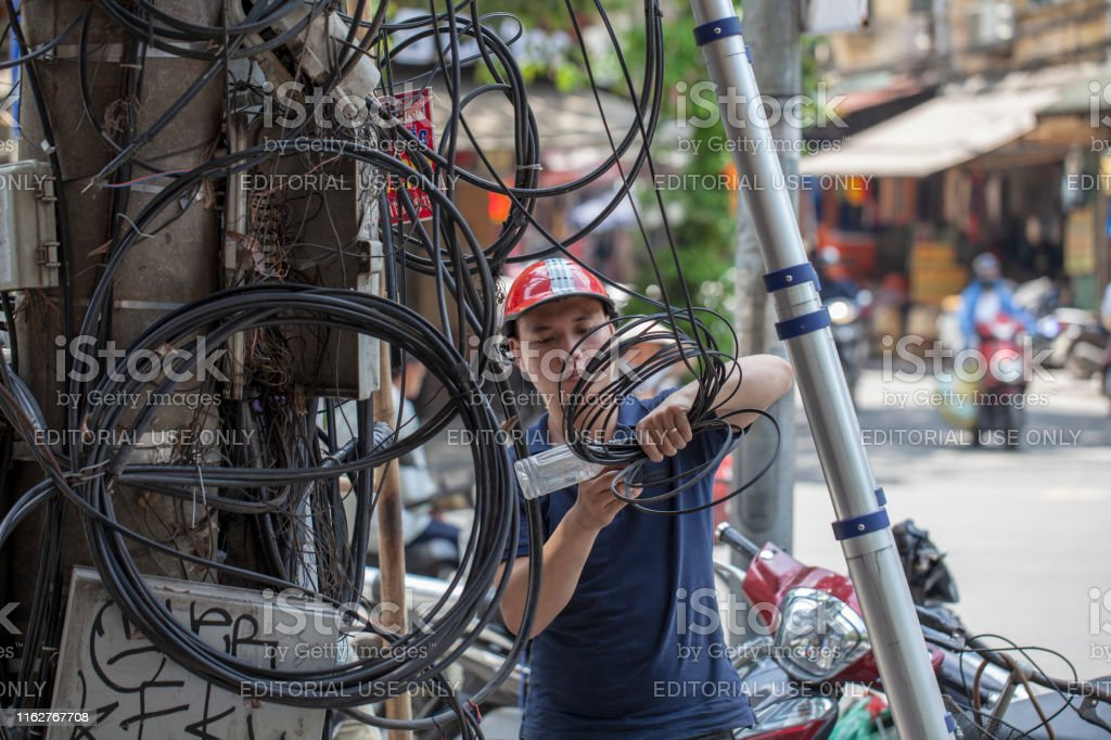 Vietnamese electrical networks. Electrical wires on poles in Hanoi. A...