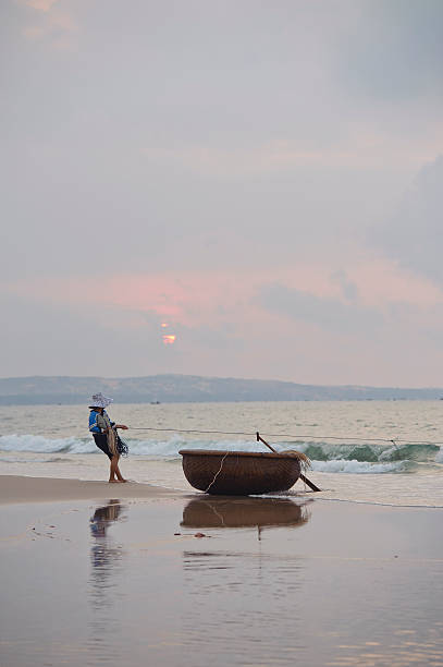 Vietnamese fisherwoman fishing with a net from the shore stock photo