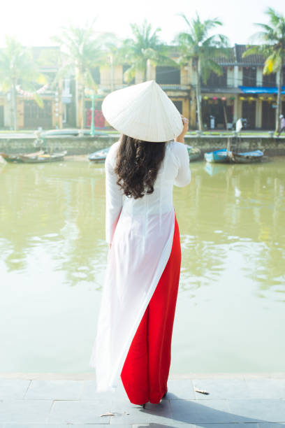 vietnamese girl is traditional dressing ao dai and non la hat is standing at riverside in hoi an heritage village in vietnam. - ao dai stock photos and pictures