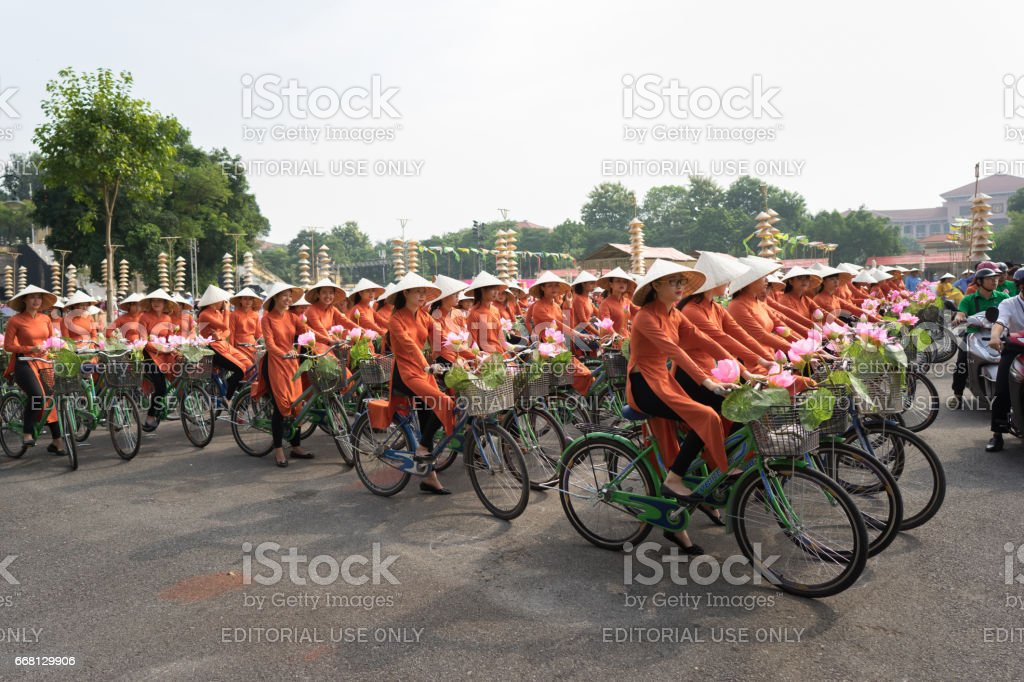 Hanoi, Vietnam - Oct 16, 2016: Vietnamese girls wear traditional long dress Ao Dai cycling on Hanoi street stock photo