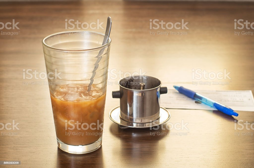 Vietnamese ice coffee with condensed milk, cafe sua da on a wooden background stock photo