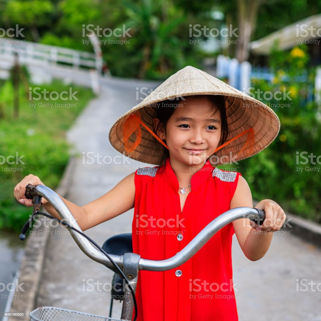 Vietnamese little girl holding a bicycle, Mekong River Delta, Vietnam stock photo