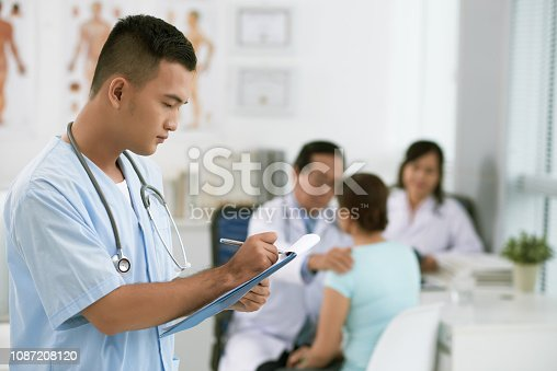 Side view of Asian male intern taking notes