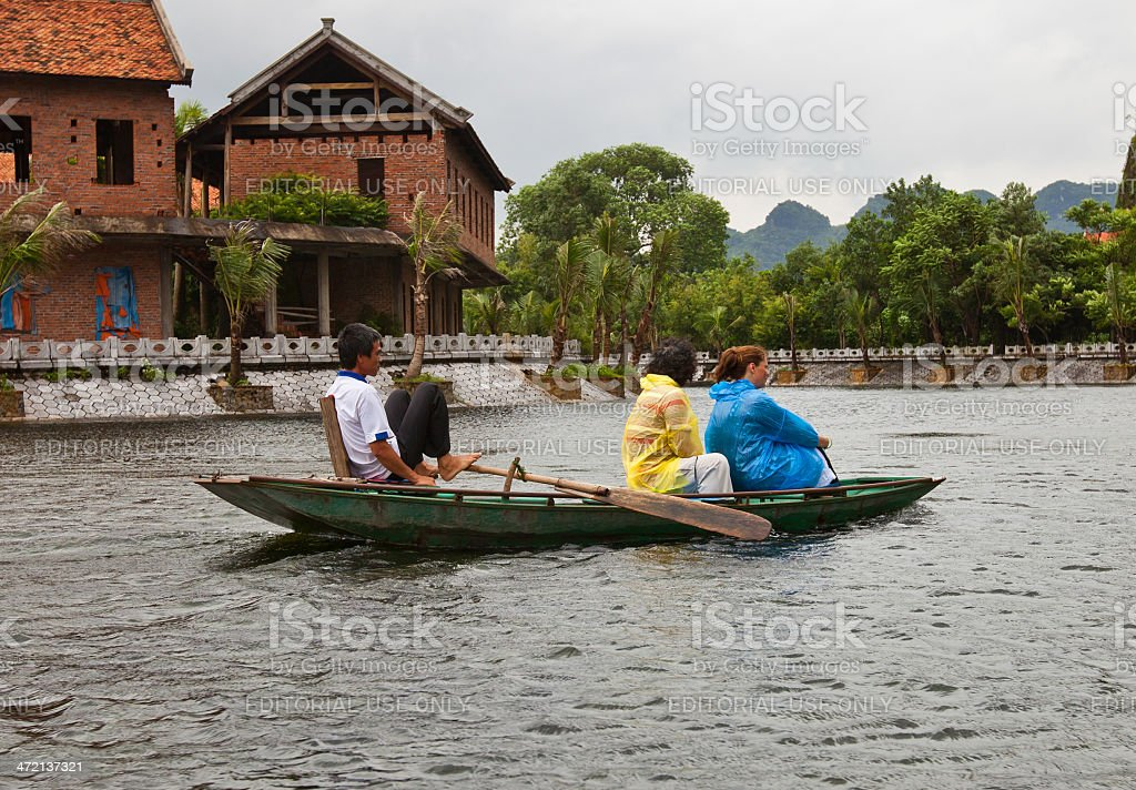 Vietnamese man gives boat ride for two tourists royalty-free stock photo