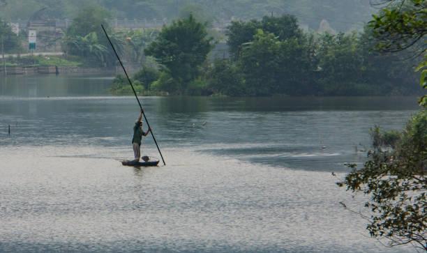 vietnamesischer mann bewegt kleines boot mit stange - holu stock-fotos und bilder