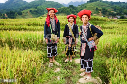 Red Dao women usually wear a long blouse over trousers and traditional red hat.