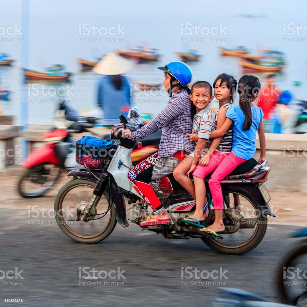 Vietnamese mother with children riding a motorbike, South Vietnam stock photo