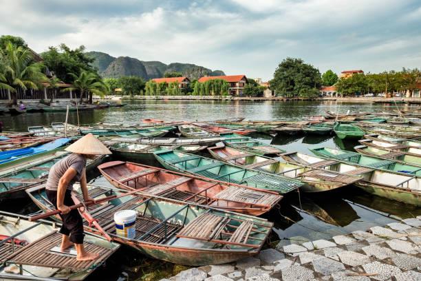 vietnamesischer paddler mit langschwanz-booten tradition im norden auf pier verankert - holu stock-fotos und bilder