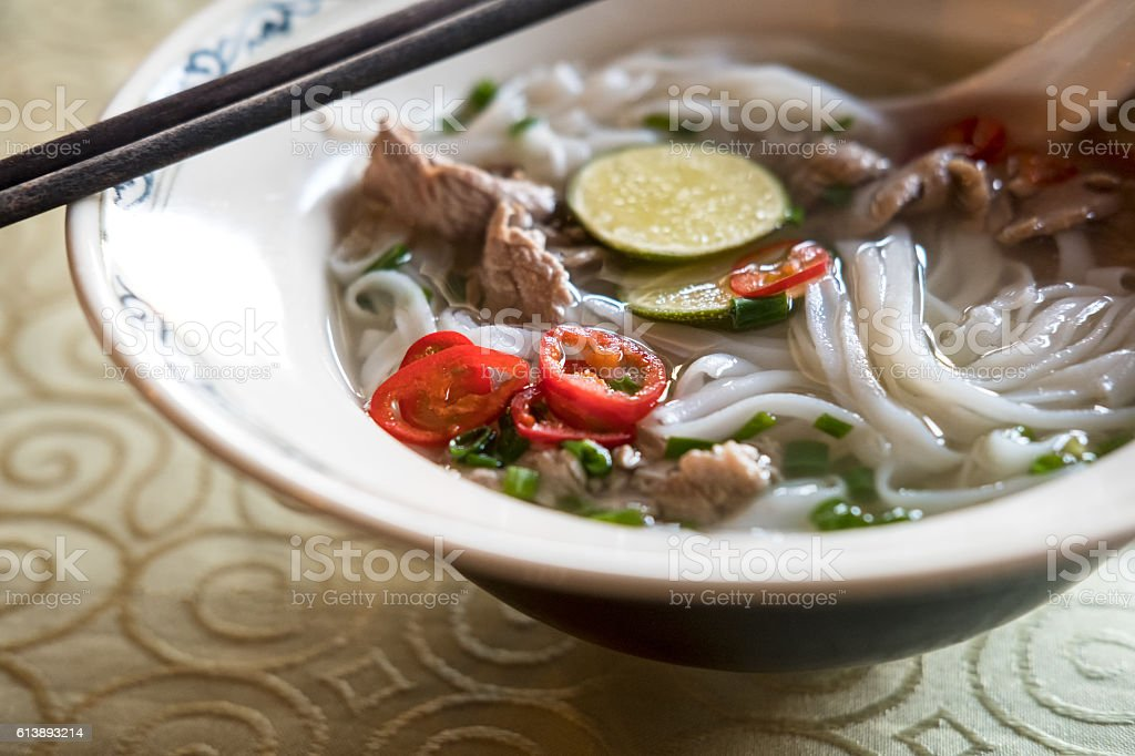Vietnamese Pho Bo,  Beef Noodle Soup, Limes, Red Chili Peppers stock photo