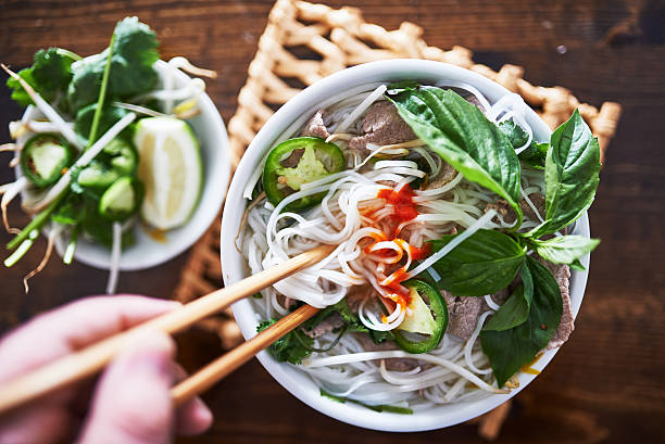 vietnamese pho with spicy sriracha sauce shot top down vietnamese pho with spicy sriracha sauce shot top down rice noodles stock pictures, royalty-free photos & images
