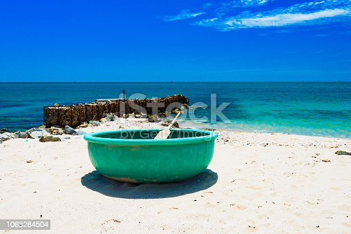traditional Vietnamese round boat with a paddle on the sandy coast of the South China Sea