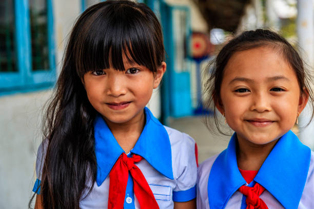 Vietnamese schoolgirls on a schoolyard, South Vietnam Happy Vietnamese schoolgirls on a schoolyard, South Vietnam vietnamese culture stock pictures, royalty-free photos & images