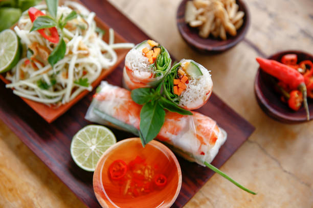Vietnamese shrimp spring rolls Food shot of sliced Vietnamese shrimp spring rolls with dipping sauce and some condiments vietnamese culture stock pictures, royalty-free photos & images