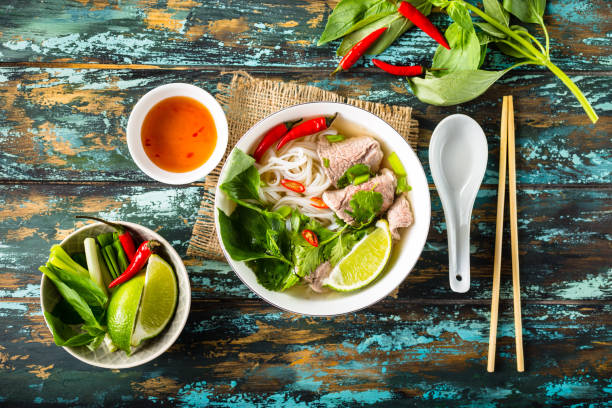 Vietnamese soup pho bo Traditional Vietnamese soup Pho bo with herbs, meat, rice noodles, broth. Pho bo in bowl with chopsticks, spoon. Space for text. Top view. Asian soup Pho bo on wooden table background. Vietnamese soup exoticism stock pictures, royalty-free photos & images