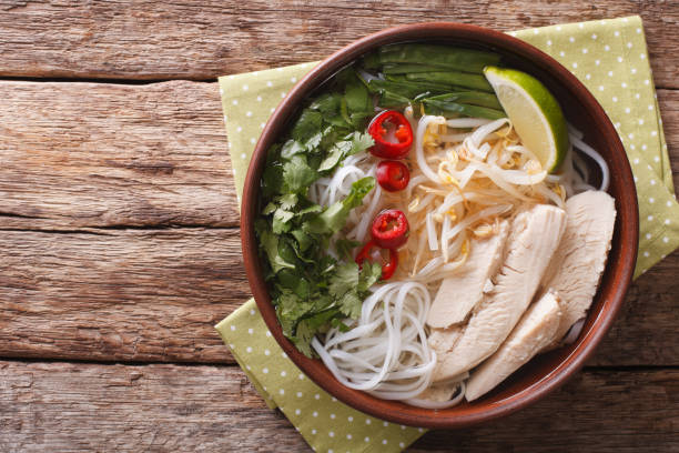 vietnamese soup pho ga with chicken and rice noodles, bean sprouts close-up. horizontal top view - pho soup stock photos and pictures