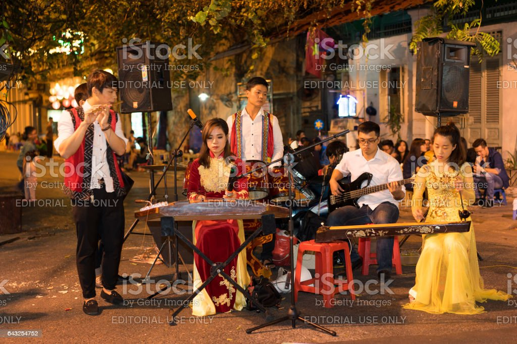 Hanoi, Vietnam - Nov 2, 2014: Vietnamese traditional folk band perform on Ma May street at night, old quarter of Hanoi stock photo