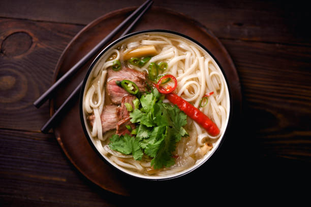vietnamese traditional soup pho bo with beef and fresh coriander on dark wooden background - pho soup stock photos and pictures