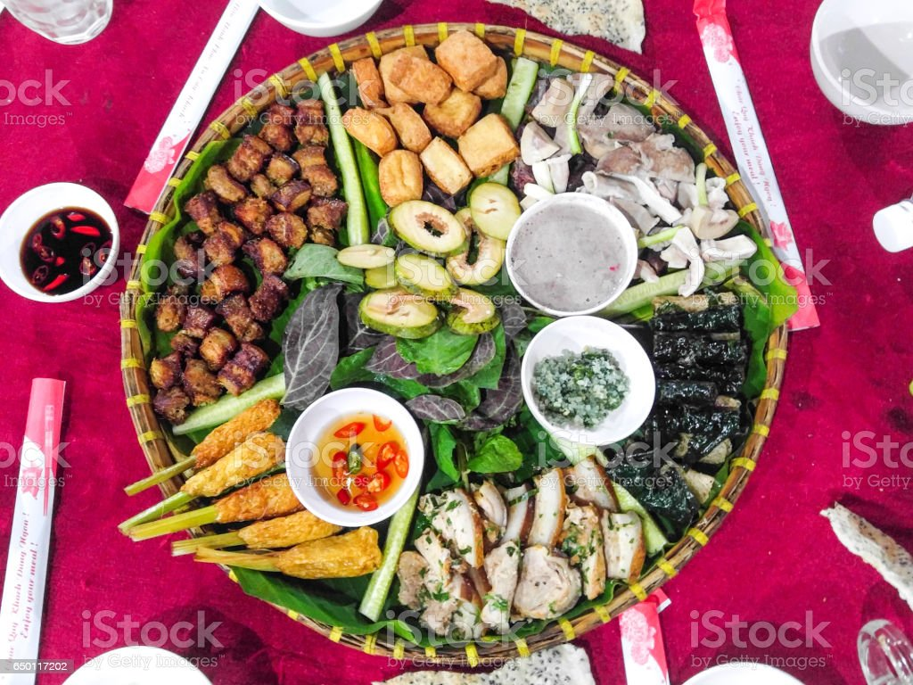 Vietnamese traditional variety food is presented on a bamboo plate...