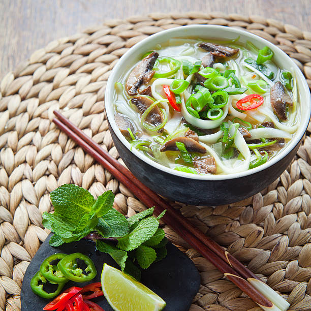Vietnamese vegan vegetarian noodle soup -  pho tom . Vietnamese vegan vegetarian  noodle soup called pho tom , Tasty traditional broth with rice noodles, spring onions,  bird's eye green, red chilies and shiitake mushrooms. Decorated with piece of fresh lime, leaves of mint, basil and slices of spicy peppers. All in bowl with chopsticks on natural wooden background. rice noodles stock pictures, royalty-free photos & images