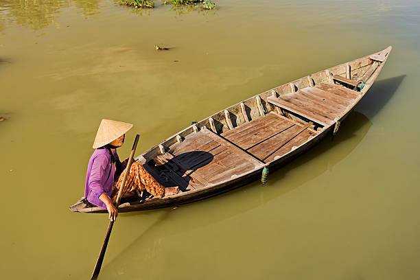 vietnamese water taxi in hoi an - ao dai stock photos and pictures