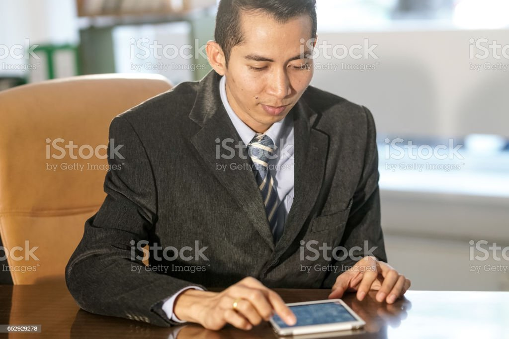 Vietnamese white collar worker sitting at desk and using his tablet...