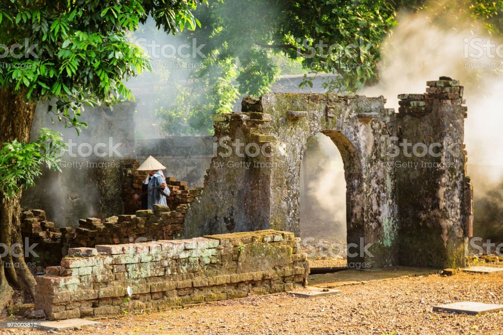 Vietnamese woman among ruins of old buildings, Hue, Vietnam Unknown Vietnamese woman in traditional bamboo hat among scenic ruins of old buildings at the Tu Duc Royal Tomb in Hue, Vietnam. Hue is a popular tourist destination of Asia. Adult Stock Photo