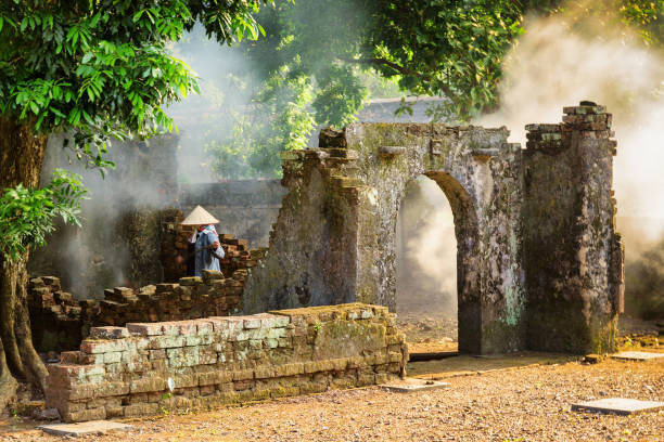Vietnamese woman among ruins of old buildings, Hue, Vietnam Unknown Vietnamese woman in traditional bamboo hat among scenic ruins of old buildings at the Tu Duc Royal Tomb in Hue, Vietnam. Hue is a popular tourist destination of Asia. huế stock pictures, royalty-free photos & images