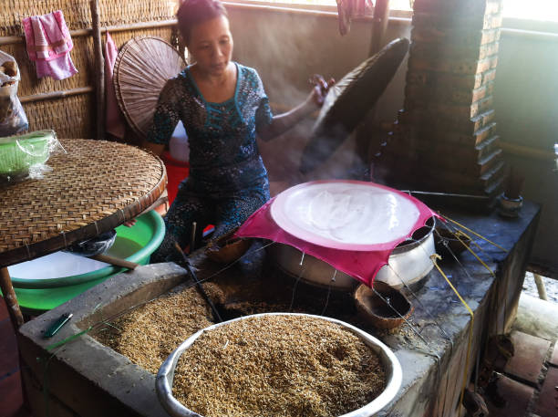 Vietnamese woman cooking rice paper on a traditional oven in a local marketplace stock photo