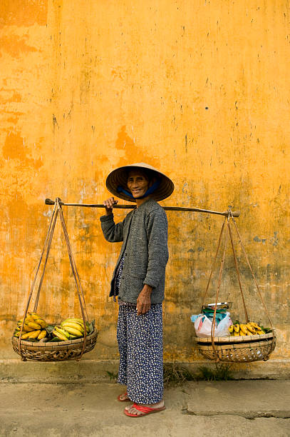vietnamese woman copy space yellow wall asian vietnamese ethnicity traditional culture asian market stock pictures, royalty-free photos & images