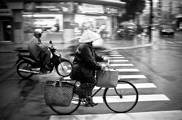 vietnamese woman cycling in the rain in nha trang - motorbike, umbrella stock pictures, royalty-free photos & images