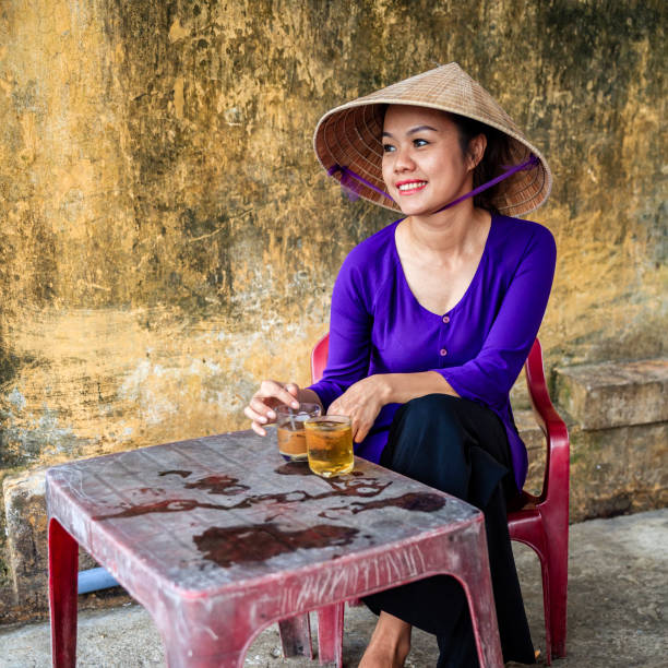 vietnamese woman drinking traditional iced coffee - cafe sua da, old town in hoi an city, vietnam - ao dai stock photos and pictures