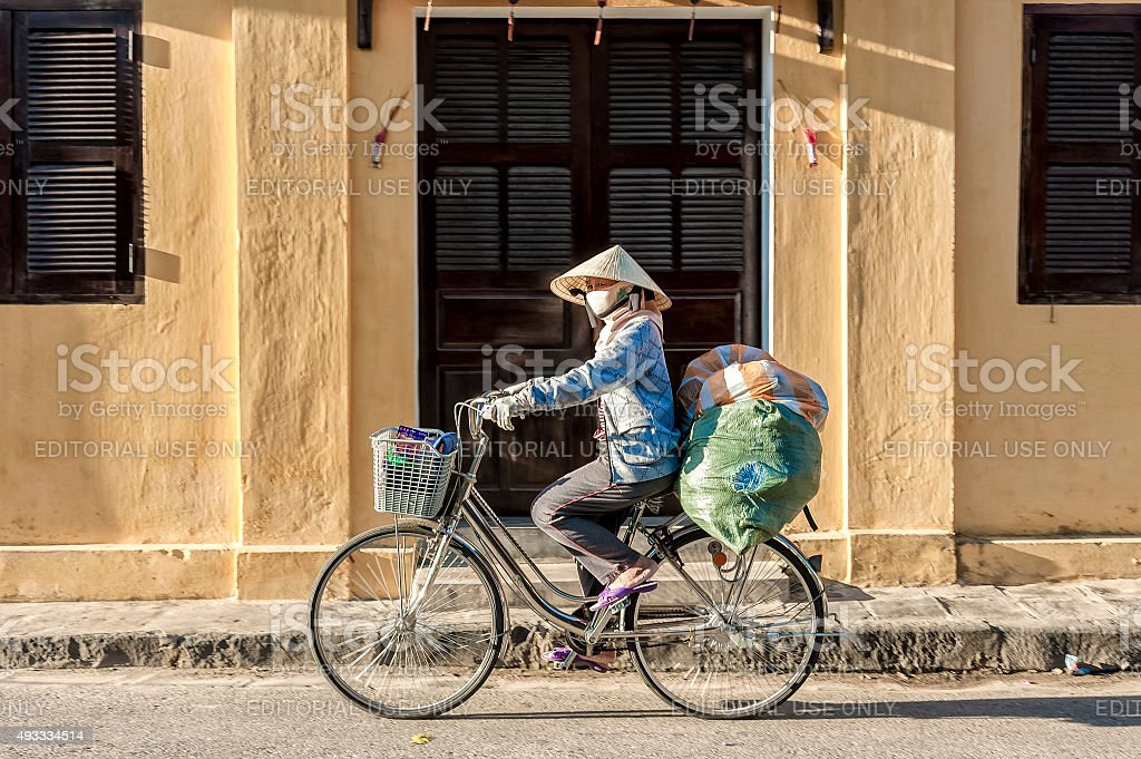 Vietnamese woman drives heavy loading bicycles stock photo