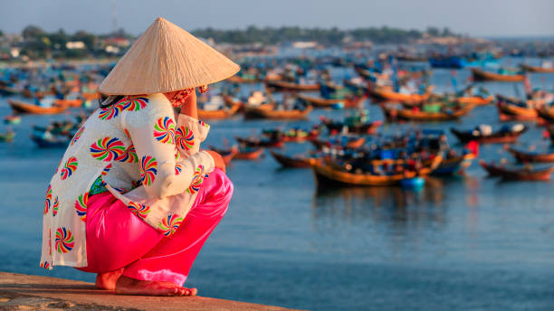 vietnamese woman looking at fishermen's boats, vietnam - ao dai stock photos and pictures