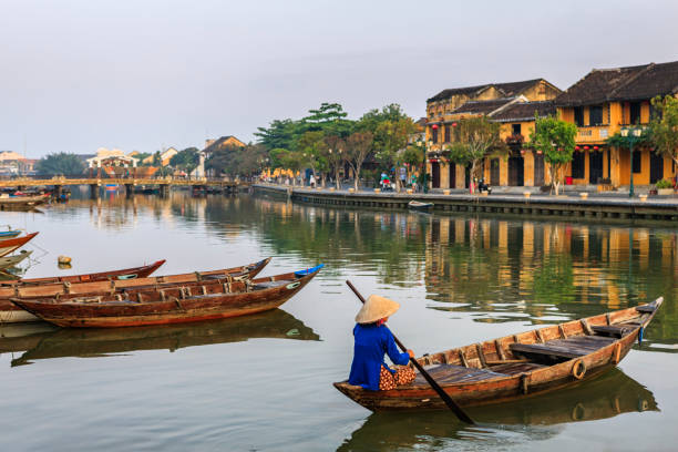 Vietnamese woman paddling in old town in Hoi An city, Vietnam stock photo
