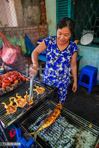 Vietnamese woman preparing grilled frogs and fishe, Mekong River Delta, Vietnam