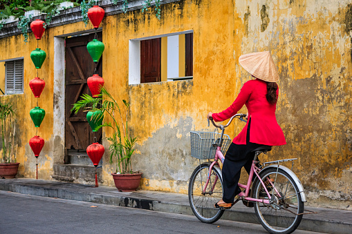 Vietnamese woman riding a bicycle, old town in Hoi An city, Vietnam