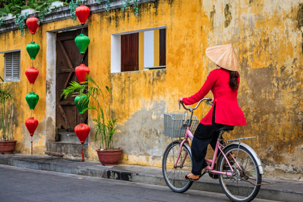 Vietnamese woman riding a bicycle, old town in Hoi An city, Vietnam stock photo