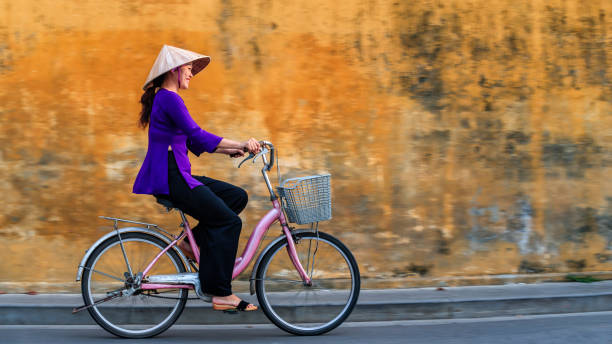 vietnamese woman riding a bicycle, old town in hoi an city, vietnam - ao dai stock photos and pictures