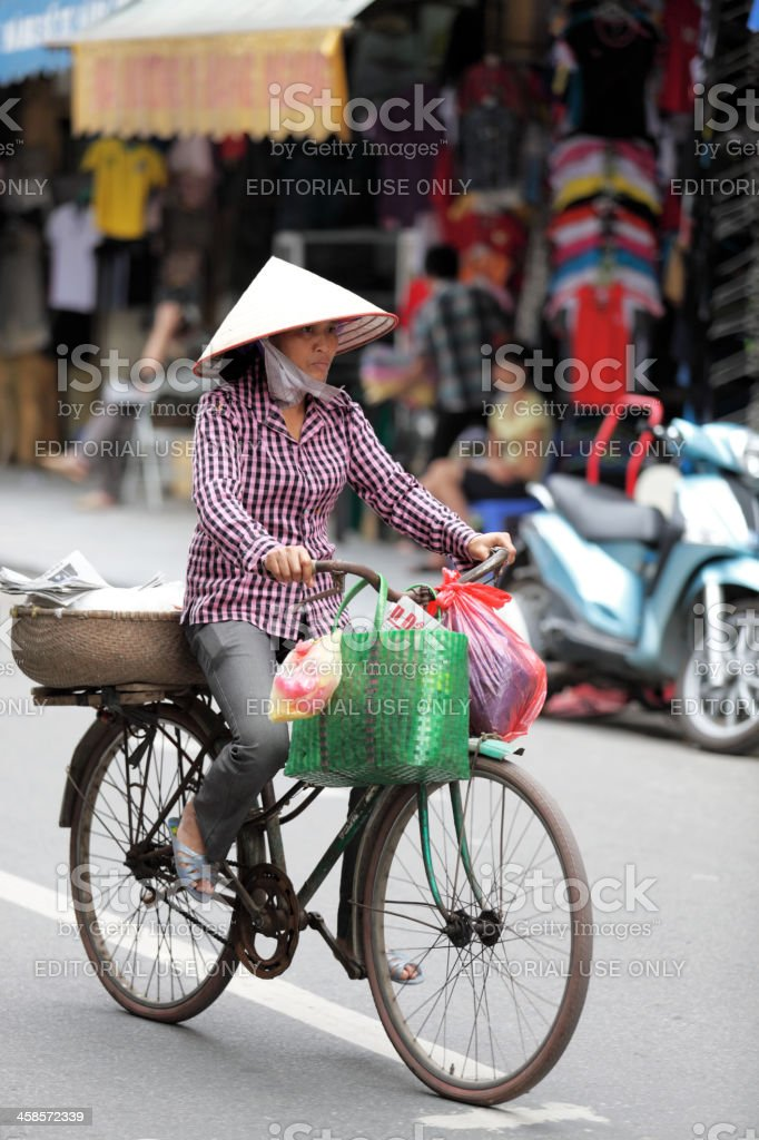 Vietnamese Woman Riding A Bicycle royalty-free stock photo