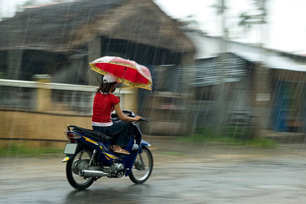vietnamese woman riding a motorcycle while holding an umbrella - motorbike, umbrella stock pictures, royalty-free photos & images