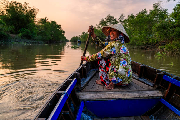 Vietnamese woman rowing a boat, Mekong River Delta, Vietnam Vietnamese woman rowing a boat, Mekong River Delta, Vietnam vietnamese ethnicity stock pictures, royalty-free photos & images