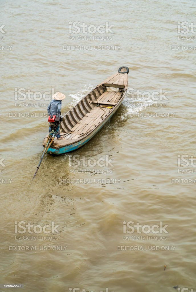Vietnamese woman rowing wooden boat on river stock photo